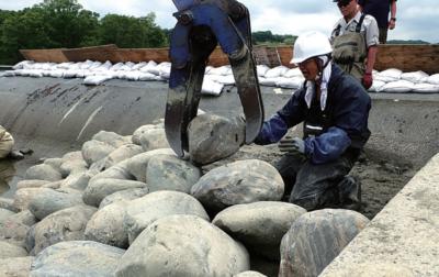 石の位置を見て重機に指示を出す安田教授