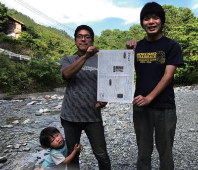 新聞を手にする松岡さん(右)と小西さん